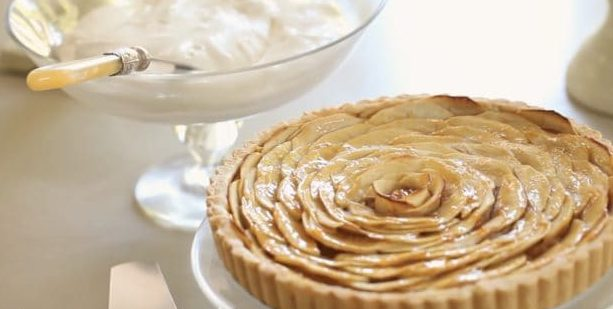 French Apple Tart on a clear cake stand with whipped cream in the background