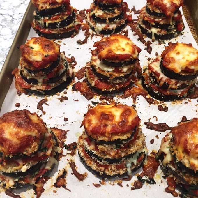 A rimmed baking sheet with 9 Eggplant Parmesan Stacks