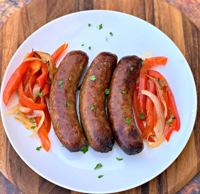 cooked air fryer sausage on a plate with peppers